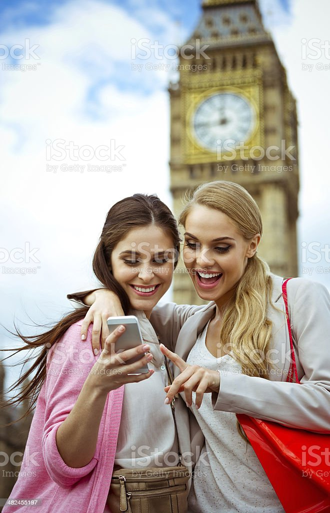 Friends in London Outdoor portrait of two happy women using a smart phone together with a Big Ben in the background. 20-24 Years Stock Photo