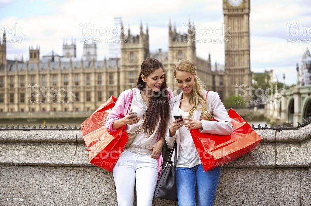 Friends in London Outdoor portrait of two happy girls using a smart phones with a House of Parliament and Big Ben in the background. 20-24 Years Stock Photo