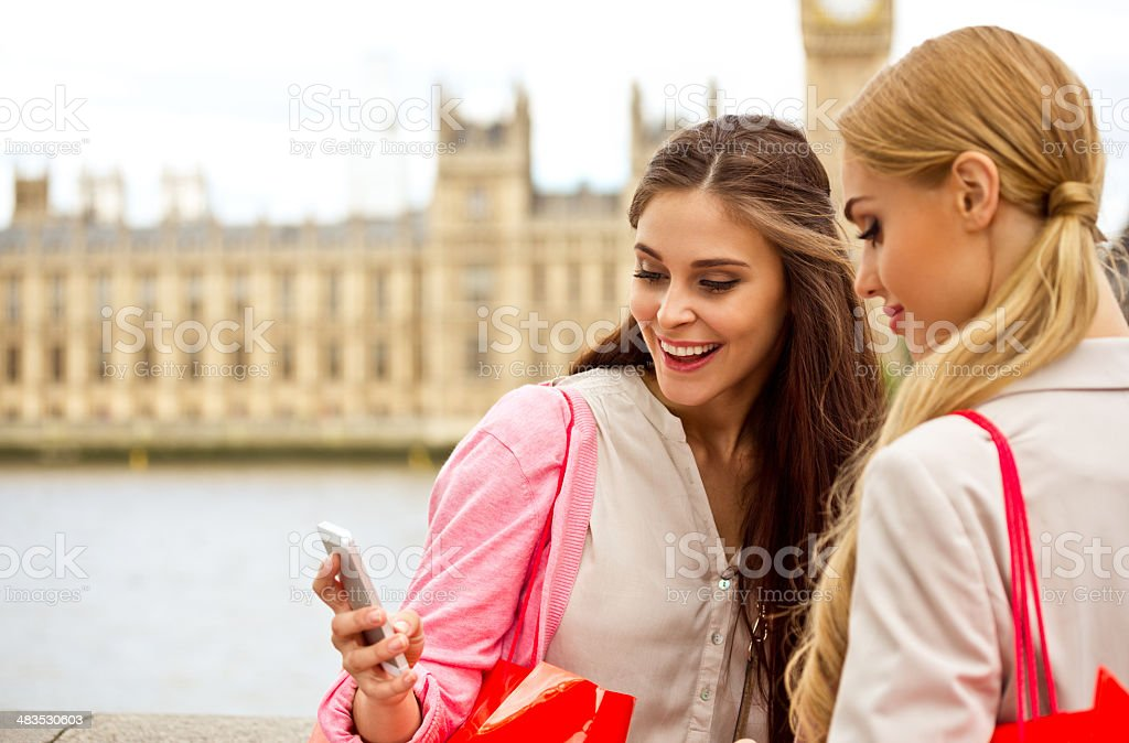 Friends in London Outdoor portrait of two happy girls using a smart phone with a House of Parliament in the background. 20-24 Years Stock Photo