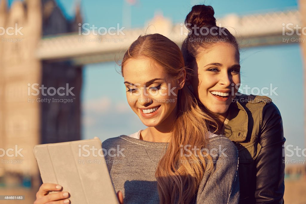 Friends in London Outdoor portrait of two happy young women using a digital tablet with Tower Brigde in the background. 20-24 Years Stock Photo