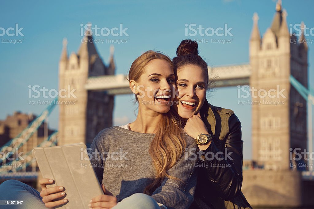 Friends in London Outdoor portrait of two happy young women taking a self picture using a digital tablet with Tower Brigde in the background. 20-24 Years Stock Photo