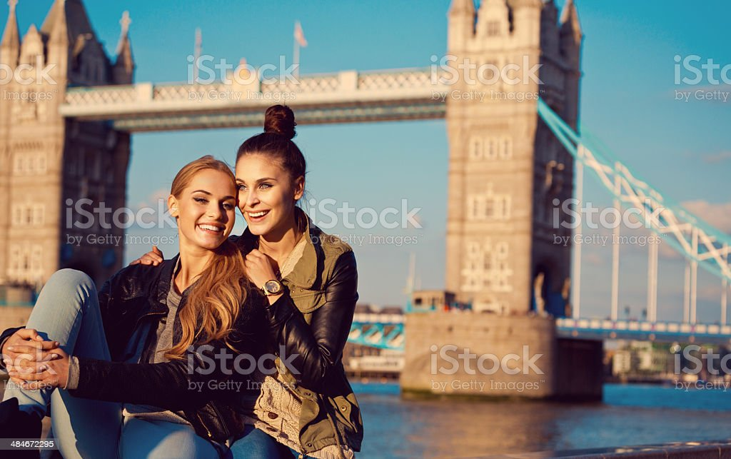 Friends in London Outdoor portrait of two happy young women smiling at camera with Tower Brigde in the background. 20-24 Years Stock Photo