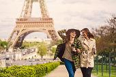 Two friends taking a walk around the Eiffel Tower in Paris.