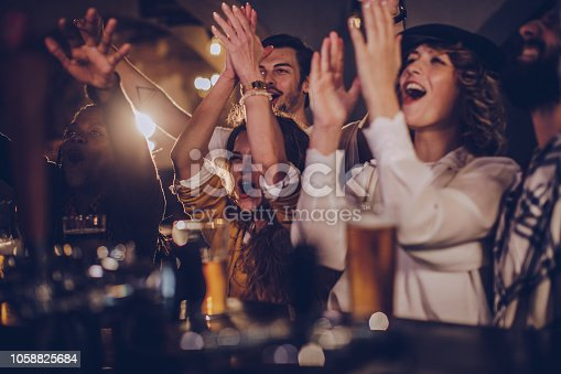 istock Friends in pub watching match 1058825684