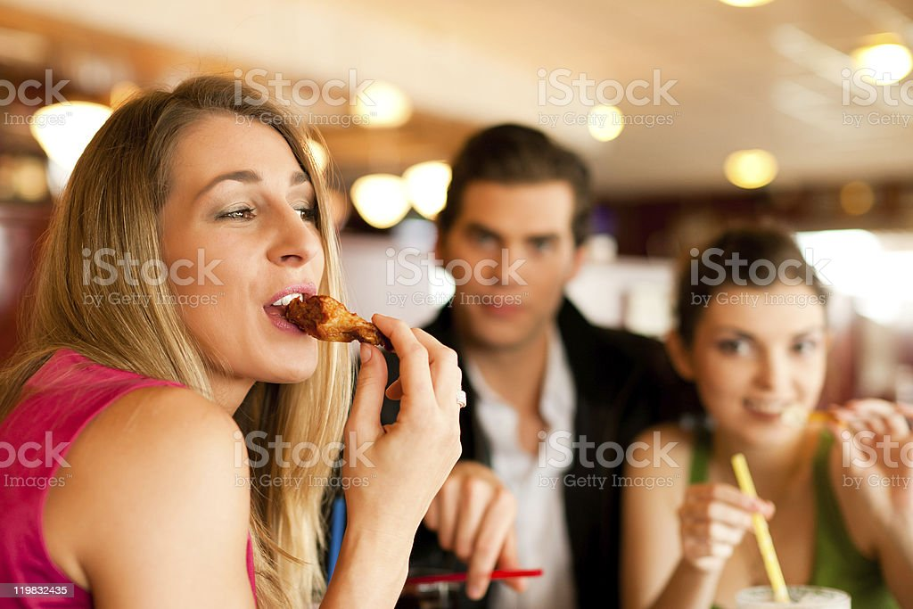 Friends in Restaurant eating fast food stock photo