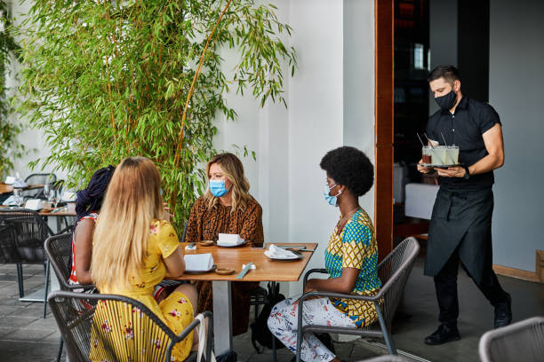 Friends In Restaurant With Face Masks - New Normal Friendship Concept stock photo