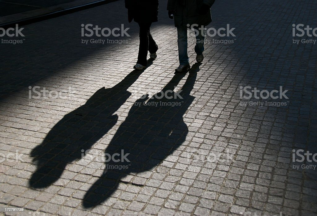 Friends in Shadow Walking on Cobblestone Street stock photo
