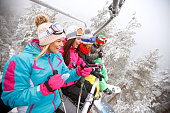 Friends in ski lift on mountain lifting on ski terrain