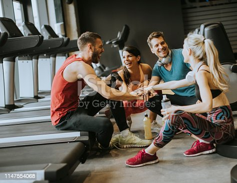 Group of young people in sportswear talking and laughing together while sitting on the floor of a gym after a workout