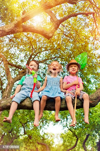 Happy children sitting on a tree bench in park