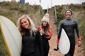 Small group of surfers walking onto the beach while holding their surfboards. They are talking and laughing as they walk.