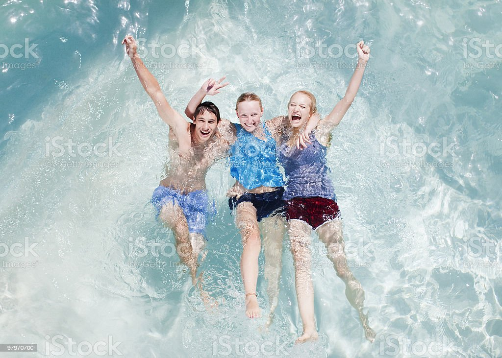 Friends in swimming pool with arms raised royalty-free stock photo