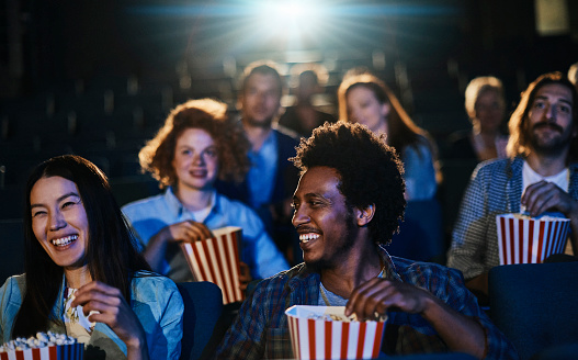 Close up of a group of friends enjoying a movie in the cinema