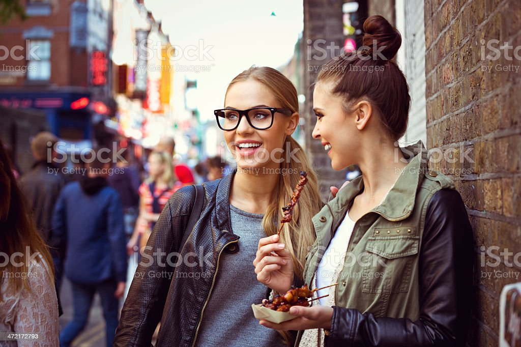 Friends in the city Two cheerful young women standing on the city street and eating street food.  20-24 Years Stock Photo