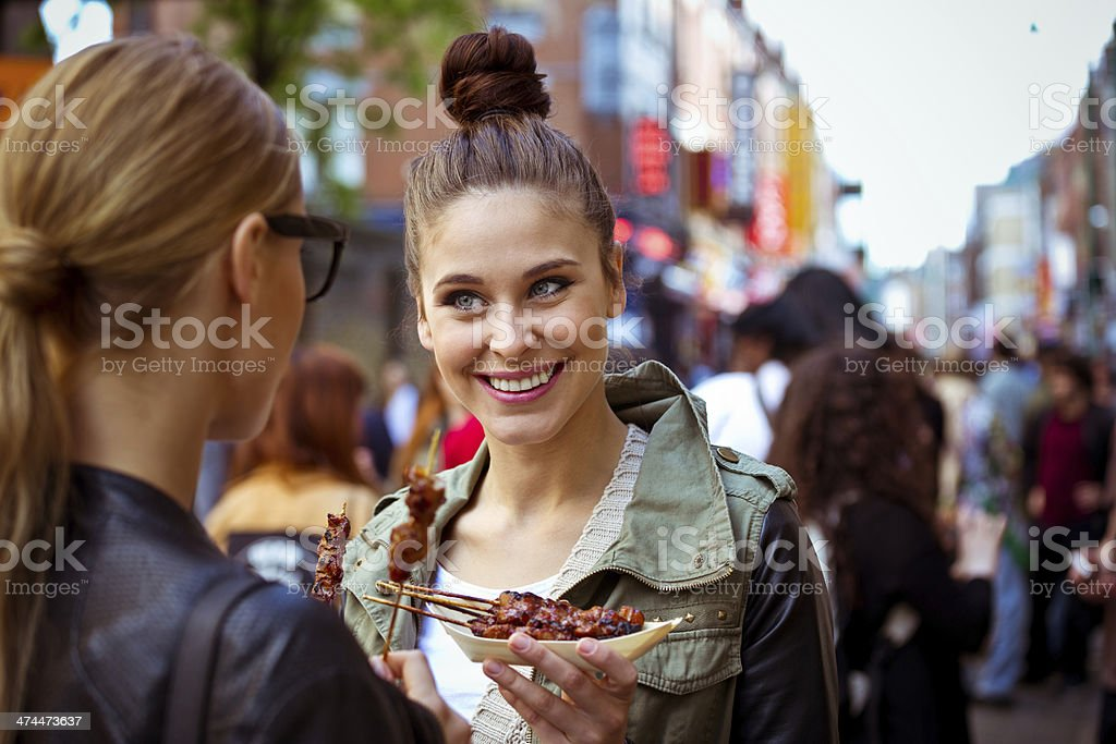 Friends in the city Smiling young women standing on the city street, eating street food and talking with her friend. 20-24 Years Stock Photo
