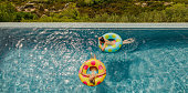Two girlfriends with inflatable rings in the infinity pool