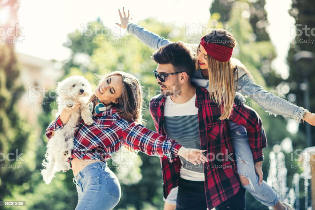 Friends in the park having fun with cute puppy royalty-free stock photo