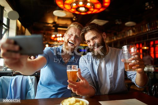 istock Friends in the pub taking a selfie image while drinking beer 999064234