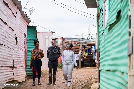 Three African friends walking together through the alleys of the rural township in Cape Town, South Africa