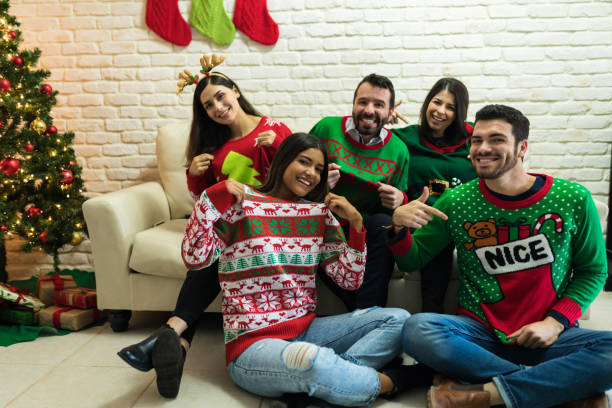 Friends In Ugly Sweater Celebrating Christmas Together At Home Cheerful friends showing off their ugly sweater while enjoying Christmas party at home ugliness stock pictures, royalty-free photos & images