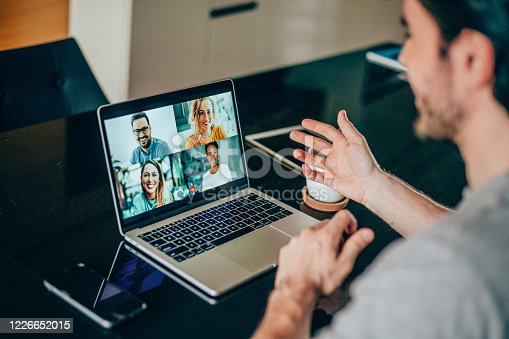 Shot of young man talking to his friends in video call from home. Multi-ethnic group of people using laptop for a online meeting in video call. Friends having online conversation during quarantine.