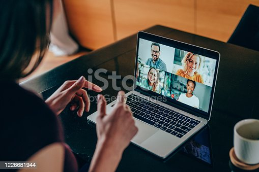 Shot of young woman talking to her friends in video call from home. Multi-ethnic group of people using laptop for a online meeting in video call. Friends having online conversation during quarantine.
