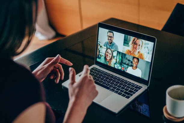 Friends in video call Shot of young woman talking to her friends in video call from home. Multi-ethnic group of people using laptop for a online meeting in video call. Friends having online conversation during quarantine. desolation stock pictures, royalty-free photos & images