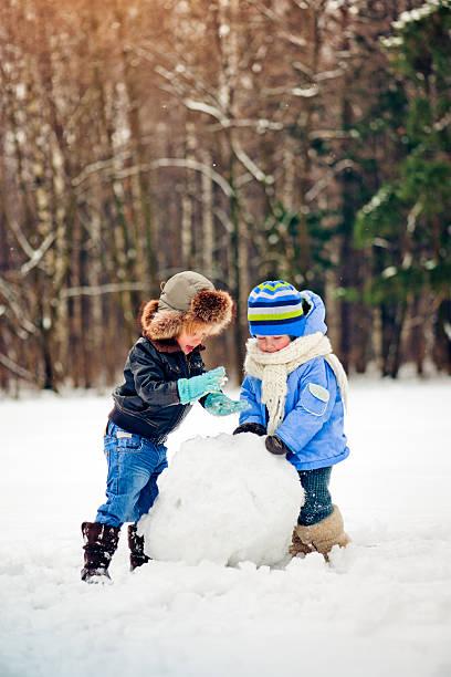 freunde in winter park - schneemann bauen stock-fotos und bilder