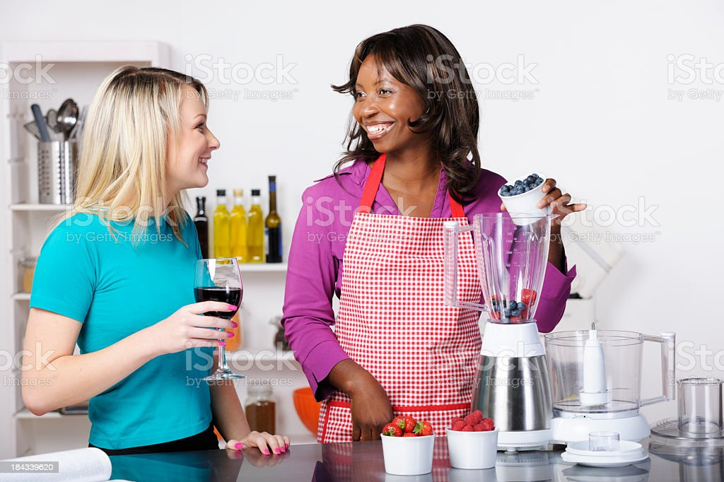 Friends Interacting While Preparing Healthy Drink/ Dessert In A Kitchen royalty-free stock photo