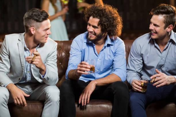 freunde, die miteinander interagieren, während mit zigarre und whisky in der bar - club sofa stock-fotos und bilder