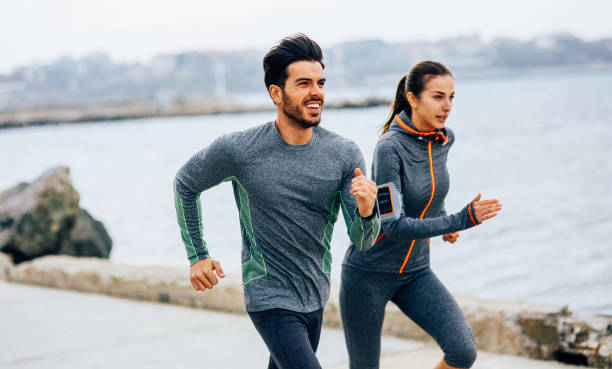 freunde, joggen am meer - armband water stock-fotos und bilder