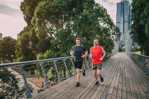Two male friends jogging in a city park.