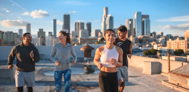 Freunde joggen gemeinsam in der Stadt gegen Himmel – Foto