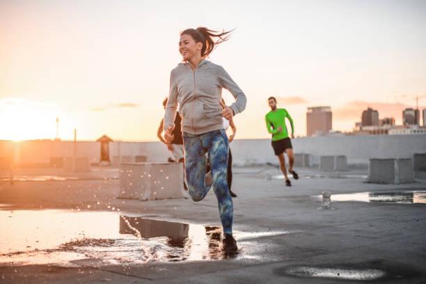Friends jogging together on terrace against sky stock photo