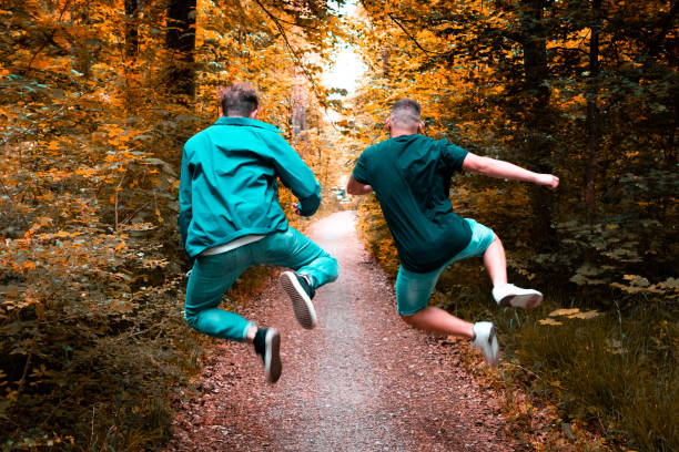 Friends jumping full of joy along forest walkway stock photo
