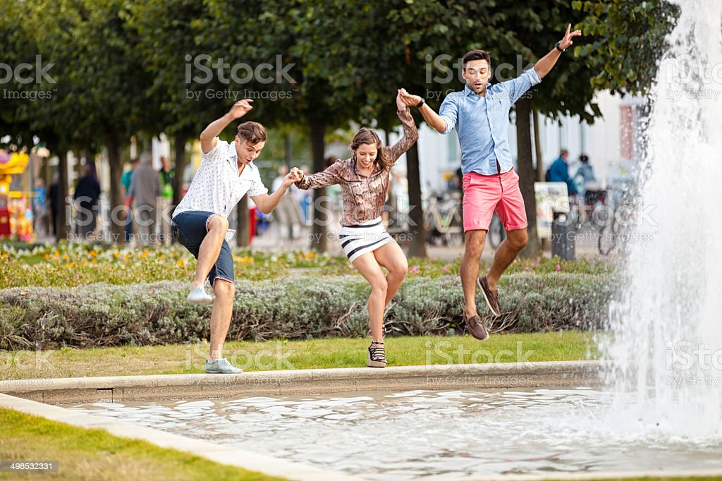 Friends Jumping Into Fountain stock photo