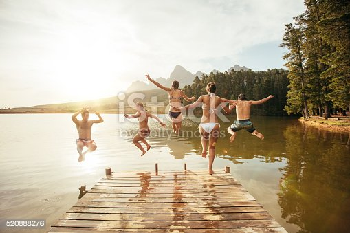 istock Friends jumping into the water from a jetty 520888276