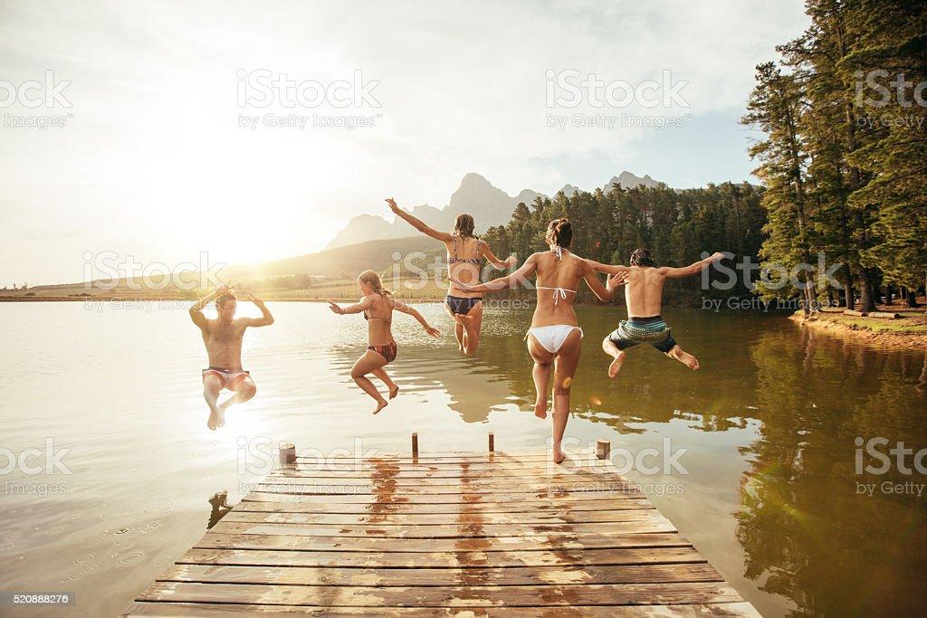 Amigos de saltar para um água de um deque - foto de acervo