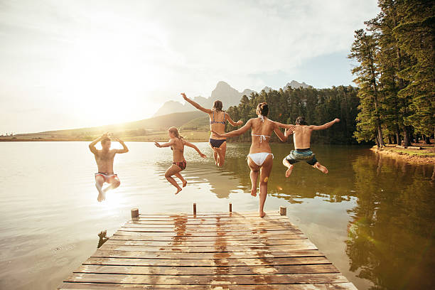 friends jumping into the water from a jetty - jumping into water stock pictures, royalty-free photos & images