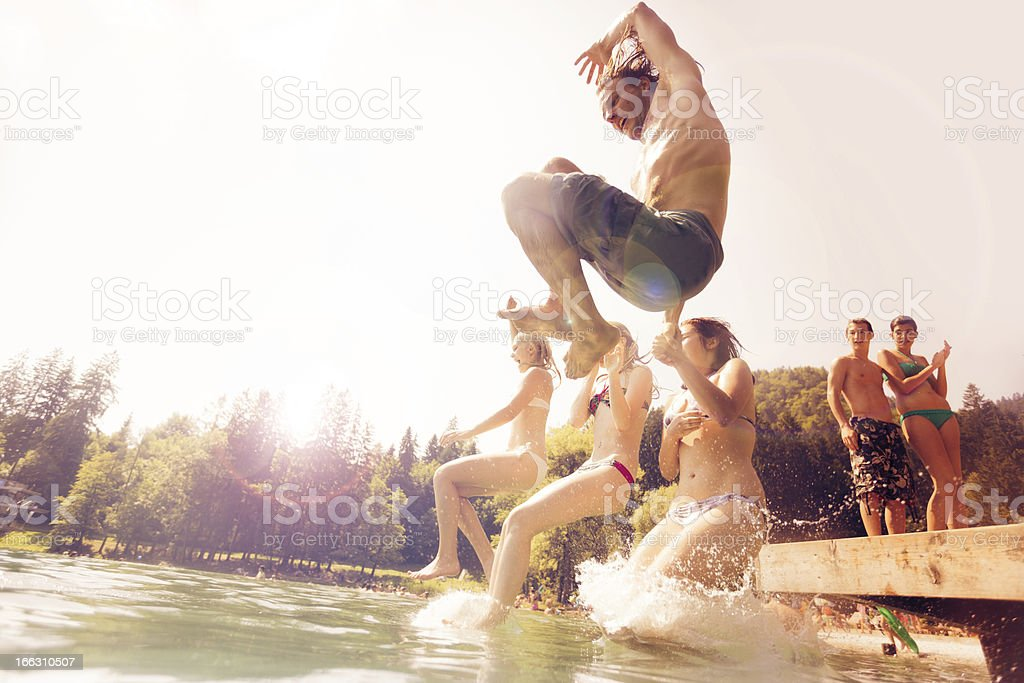 friends jumping into the water stock photo