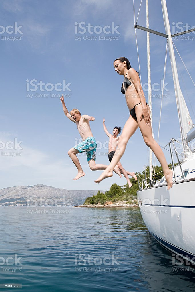 Friends jumping off a yacht 免版稅 stock photo