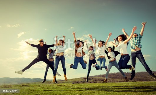 happy friends jumping in summer field, arms raised.