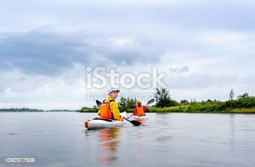 Male and female friends kayaking in Laugarvatn lake. They are enjoying vacation. Image is representing tranquil nature.