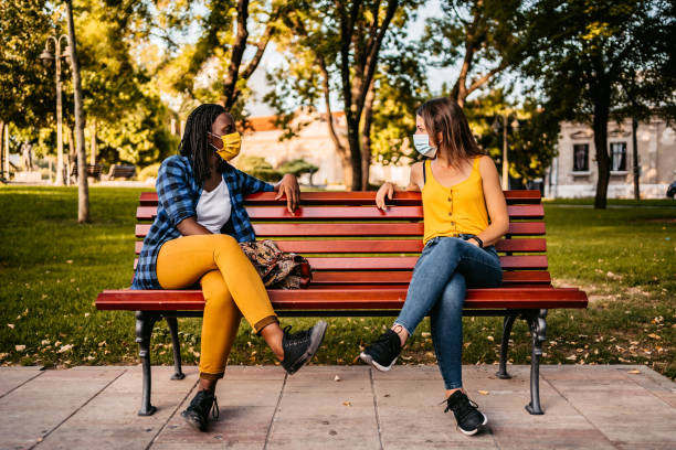 Friends keeping social distance on bench stock photo
