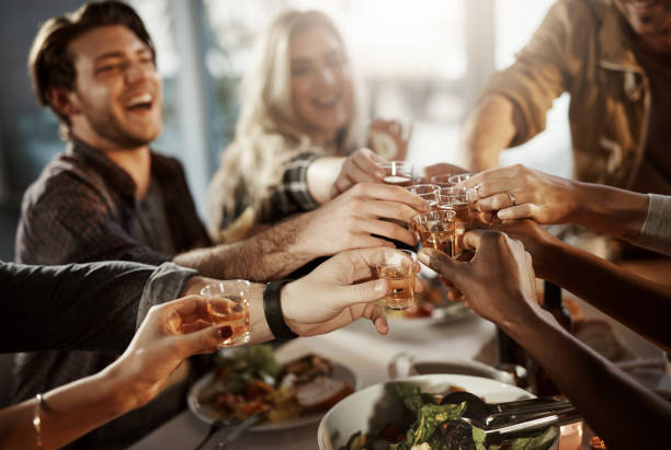 Friends know how to have fun Shot of a group of young friends making a toast at a dinner party vodka stock pictures, royalty-free photos & images