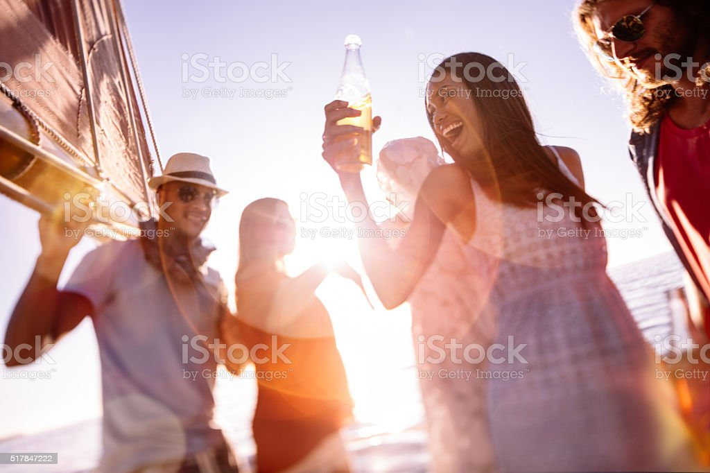 Amigos, rir e dançar num iate ao pôr do sol - fotografia de stock