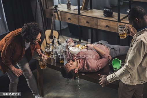 friends laughing and looking at man drinking from beer bong on table