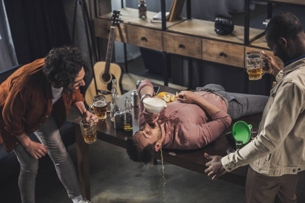 friends laughing and looking at man drinking from beer bong on table - drunk stock photos and pictures