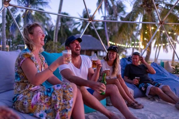 friends laughing around the bonfire on the beach at sunset - all vocabulary zdjęcia i obrazy z banku zdjęć