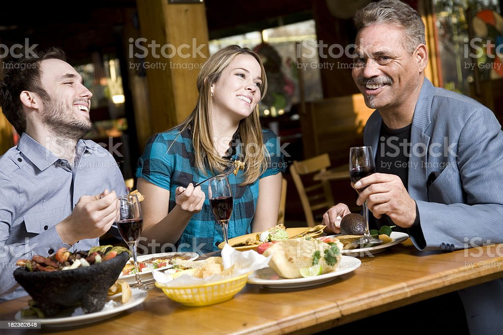 Friends Laughing at Dinner Having Mexican Food stock photo